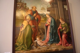 The adoration of the Infant Christ with Saints Barbara and Martin by Raffaello Botticini painted after 1520 in Florence