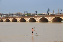 Paddleboarder in front of Pont de Pierre - Bordeaux