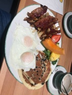 Bel's eggs, bacon, potatoes, fruit and blueberry pancakes
