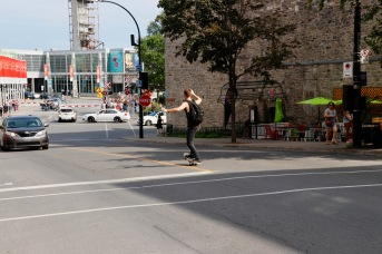 Old Montreal riding a skateboard down the hill in the middle of the road